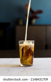 Iced Coffee being poured in a cafe on white marble with a dark background