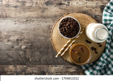 Iced coffee or caffe latte in tall glass on wooden table. Top view. Copy space