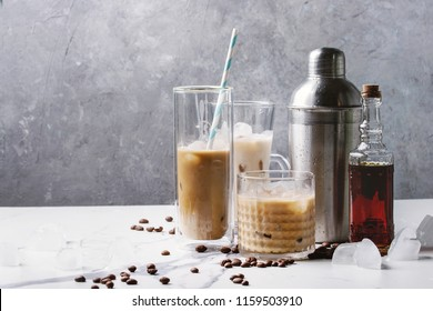 Iced coffee cocktail or frappe with ice cubes and cream in different glasses with silver shaker, bottle of rum, coffee beans around on white marble table with grey concrete wall at background.