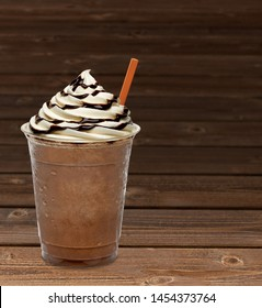 Iced coffee with cream and chocolate syrup in takeaway plastic cup on wooden table DOF