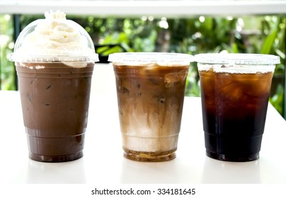 Iced coffee with cream in take away cup on white background .Collection of iced coffee on white table