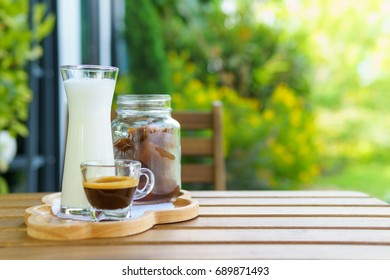 iced coffee cube latte with milk and shot of espresso on the wooden table in the garden. bright tone. with copy space for text