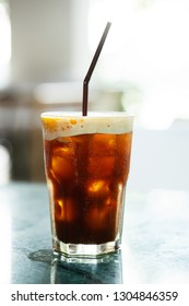 Iced coffee drink with orange slice on green marble table
