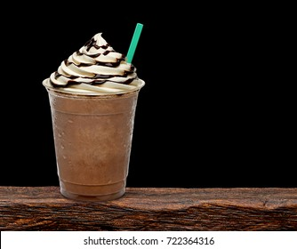 Iced coffee or frappuccino with cream in takeaway disposable cup on wooden table with black background.