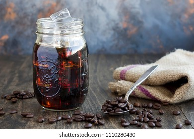 Iced coffee in a glass jar with a spoon full of coffee beans.