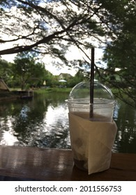 Iced coffee in glass on the table near the pond