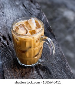 Iced coffee in a glass on wood background