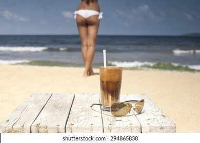 Iced coffee and glasses on a wooden table on the beach. In the distance woman in swinsuit and the sea.