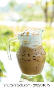 Iced coffee in jug, jar, mug glass cups on the table
