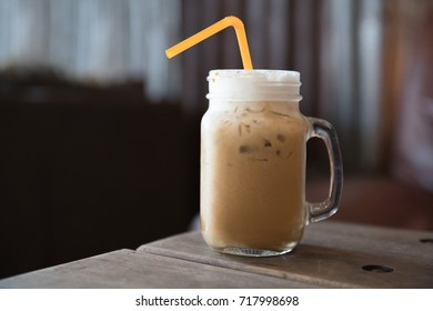 Iced coffee in a jug on the wooden table in a cafe