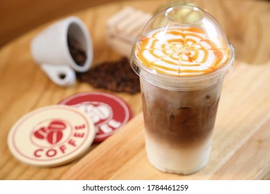 Iced Coffee Latte with Caramel Syrup on wooden background