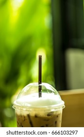 Iced coffee latte in takeaway cup isolated on nature background