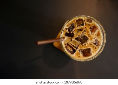 Iced coffee latte in a tall glass with cream poured over on wooden  saucer at black table. copy space. selective focus