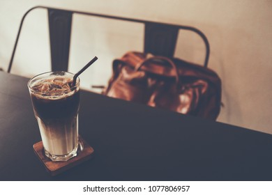 Iced coffee latte in a tall glass with cream poured over on wooden  saucer at black table and chair with leather bag. copy space. selective focus