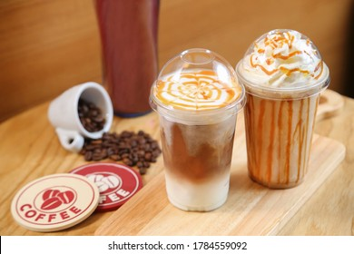 Iced Coffee Latte with Whipped Cream and Caramel Syrup on wooden background