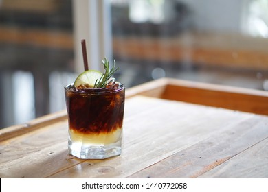 Iced coffee with lemon - A glass of espresso shot mixed with lemonade juice and honey, topped with sliced lime and rosemary leaves on blurred background and copy space, Perfect drink for summer time.
