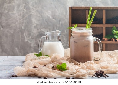 Iced coffee with milk in glass jar on wooden table decorated with cinnamon and mint