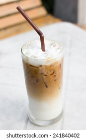 Iced coffee with milk is on the table in cafe.