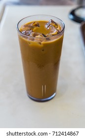 Iced coffee with milk in a tall glass on white table in Cafe shop
