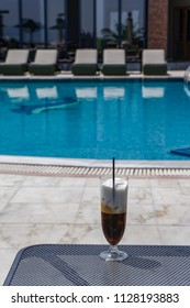 Iced coffee on a glass with plastic straw. Freddo cappuccino served in Greece with blurred pool background.
