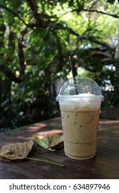 Iced coffee on a table with fallen leaves in a sunny tropical garden in Asia