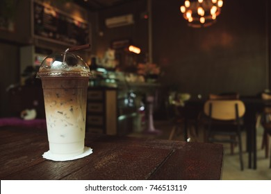 Iced coffee on wooden background in coffee shop.