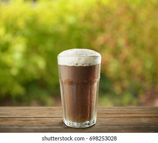 Iced coffee on wooden table in garden