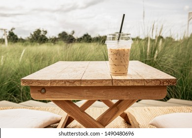 Iced coffee in plastic cup on wood table. Vintage color tone.