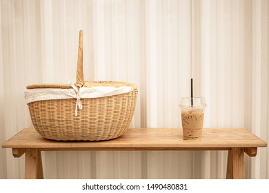 Iced coffee in plastic cup and picnic basket on wooden bench. Vintage color tone.