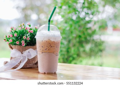 Iced coffee in plastic cups on the wooden desk with background in natural light blur and bokeh. Has copy space