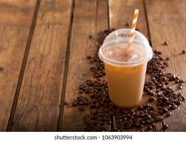 iced coffee in plastic glass with beans on wooden table