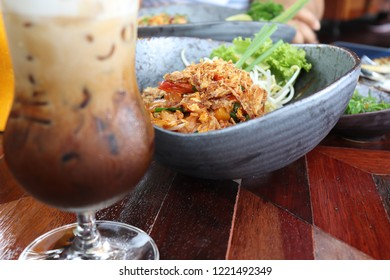 iced coffee serve with padthai or fried noodle in thai style in the ceramic big blue bowl