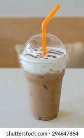 Iced coffee with straw in plastic cup