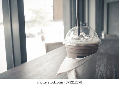 Iced coffee with straw in plastic cup (vintage effect)