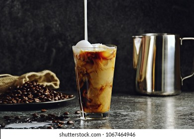 Iced coffee in a tall glass with cream poured over. Iced coffee isolated