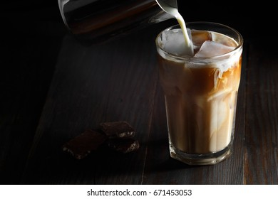 Iced coffee in a tall glass with cream poured over. Wood background. Low key.