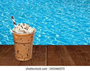 Iced coffee with whipped cream in disposable or plastic to go cup on wooden table with pool background
