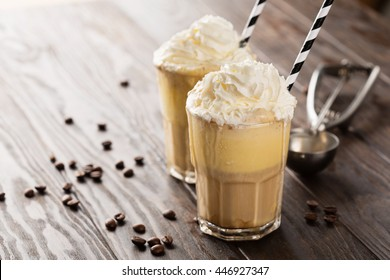 Iced coffee with whipped milk and caramel ice cream in tall glasses on rustic wooden table, selective focus