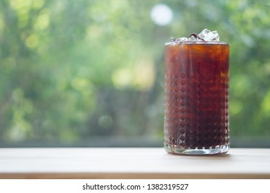 Iced cold brew coffee in glass on wooden table with nature background