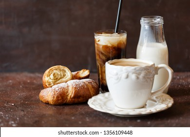 Iced cold brew coffee and hot coffee with cream and croissant. Breakfast concept