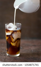 Iced cold brew coffee in a tall glass with cream poured over