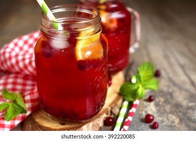 Iced cranberry tea with orange in a mason jar on rustic background.