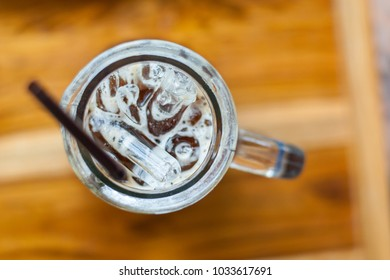 An Iced espresso coffee in tall-shape glass with brown plastic straw in the left side of photo focused on its ice from top view on wooden table, refreshing drink