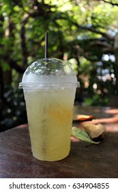 Iced Honey and Lemon Herbal Tea by fallen leaves in a sunny tropical garden in Asia