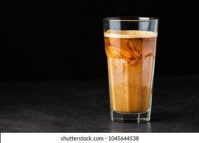 Iced latte coffee glass on a black table