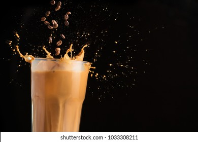 Iced latte coffee glass with splash on a black background. falling coffee beans