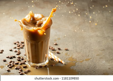 Iced latte coffee splash with ice cubes and roasted beans on a dark background. With copy space