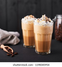 Iced latte coffee in a tall glass with caramel and chocolate syrup and whipped cream. Dark wooden background.