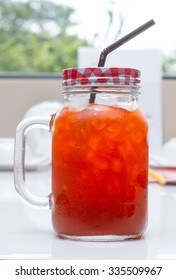 Iced Lemon tea in jar glass for drink on white table.