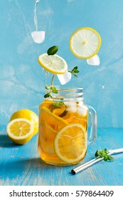 Iced lemon tea on blue background in mason jar and flying in air ingredients. Space for text
